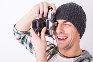 Young smiling photographer with camera on the gray background.